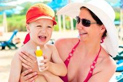 Mamá e hijo en la playa para proteger la piel contra la loción del sol Foto de archivo libre de regalías