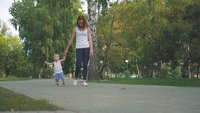 Mamá e hijo que caminan en el parque Primeros pasos del niño pequeño en parque del verano Bebé que camina en el parque con el ` s almacen de video