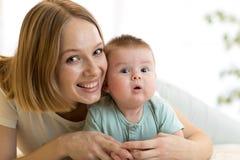 Mamá e hijo que se acuestan en cama en sitio del cuarto de niños Bebé infantil de abarcamiento de la madre Imagen de archivo libre de regalías