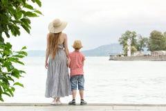 Mamá e hijo que se colocan en el embarcadero, el faro y las montañas en la distancia Visión posterior Fotografía de archivo