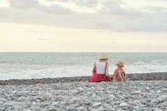 Mamá e hijo que se sientan en la playa Visión desde la parte posterior Fotos de archivo