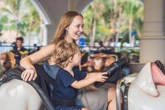 Mamá e hijo que tienen un paseo en el coche de parachoques en el parque de atracciones Fotos de archivo libres de regalías