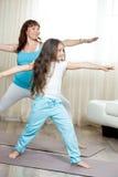 Mamá embarazada que hace yoga prenatal con su pequeña hija en el hom imagen de archivo