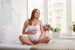 Mamá embarazada soñadora que sonríe y que mira la ventana mientras que sitt Imagenes de archivo