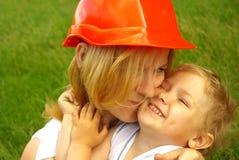 Mamá en el casco de la construcción con el amor que abraza a la hija feliz Imágenes de archivo libres de regalías