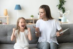 Mamá estricta que regaña a la hija mal educada que grita ruidosamente en casa foto de archivo
