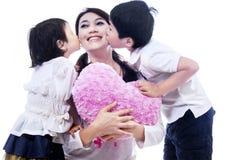 Mamá feliz besada por los niños imágenes de archivo libres de regalías