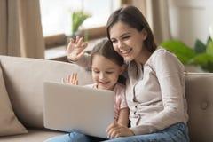 Mamá feliz con la hija del niño que mira el ordenador portátil para hacer la llamada video foto de archivo libre de regalías