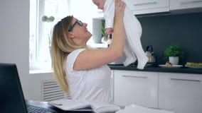 Mamá feliz del negocio con el bebé que trabaja en casa en cocina, madre y la sonrisa de dos hijos almacen de metraje de vídeo