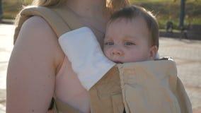 Mamá feliz joven con el bebé en ergo mochila que camina en el parque