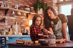 Mamá feliz que cocina con su pequeña hija en cocina del estilo del desván en la mañana imágenes de archivo libres de regalías