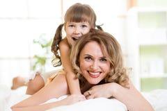 Mamá feliz que juega con su niño en el goce de la cama Fotografía de archivo