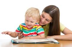 Mamá feliz que lee un libro al hijo del niño Foto de archivo