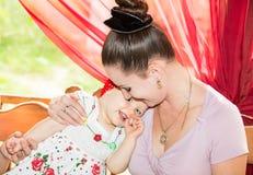 Mamá feliz y bebé que abrazan y que ríen. El concepto de niñez y de familia. Foto de archivo libre de regalías