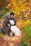 Mamá feliz y su hijo con el perro imagen de archivo