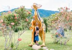 Mamá hermosa con poca hija cerca del dinosaurio anaranjado grande en el parque en un día soleado Yang Bay, Vietnam imagen de archivo