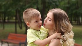 Mamá hermosa joven que detiene a su pequeño hijo en el parque para un paseo, primer almacen de metraje de vídeo