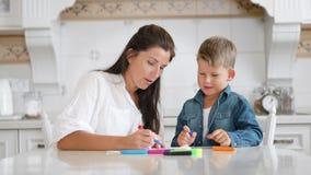 Mamá hermosa y pequeño hijo lindo que gozan uniendo la imagen usando rotulador multicolor almacen de metraje de vídeo