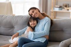 Mam? joven del abrazo feliz lindo de la hija que se sienta en el sof? imagenes de archivo