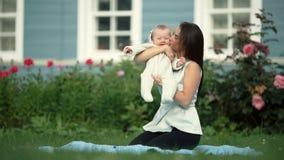 Mamá joven que juega con su pequeña hija cerca de la casa almacen de video
