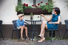 Mamá joven y su hijo en café de la calle Foto de archivo libre de regalías