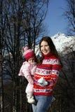 Mamá linda que detiene a su hija en sus brazos Fotos de archivo libres de regalías