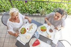 Mamá moderna e hija joven que comen el almuerzo foto de archivo libre de regalías