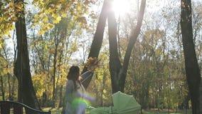 Mamá morena que aumenta su mano para arriba con un manojo de hojas y que juega con el sol en el parque