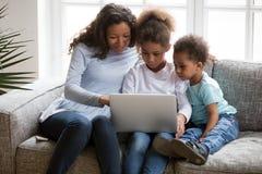 Mamá negra de la familia con los niños usando el ordenador portátil junto en casa fotos de archivo libres de regalías