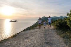Mamá, papá e hijo de la familia caminando abajo de un camino de la montaña con paisaje marino en la puesta del sol Front View Fotografía de archivo