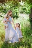 Mamá que abraza a dos hijas al aire libre Imágenes de archivo libres de regalías