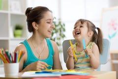 Mamá que ayuda a su niño a trabajar el papel coloreado fotos de archivo libres de regalías