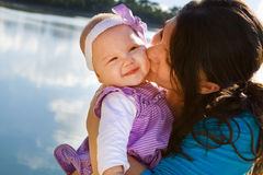 Mamá que besa a la hija del bebé por el lago Imagen de archivo libre de regalías