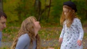 Mamá que besa a la hija en el parque metrajes