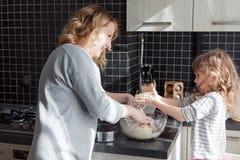Mamá que cocina con la hija foto de archivo libre de regalías
