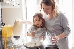 Mamá que cocina con la hija foto de archivo