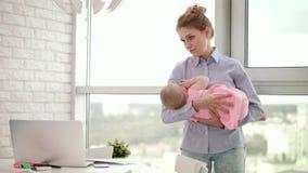 Mamá que detiene al bebé en las manos en oficina Niño durmiente en abrazo de la madre almacen de metraje de vídeo