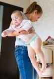 Mamá que detiene al bebé La mamá limpia la ropa del bebé fotografía de archivo libre de regalías