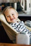 Mamá que espera sonriente linda del bebé en alta silla del cuarto de niños fotografía de archivo
