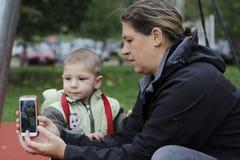 Mamá que fotografía al pequeño hijo del selfie con el teléfono móvil en parque foto de archivo