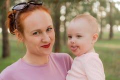 Mamá que juega con la hija en el parque, retrato cercano foto de archivo