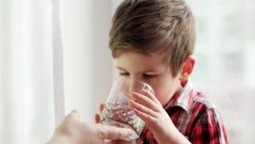 Mamá que le trae el vidrio sediento del hijo del agua, agua potable del niño pequeño del vidrio, cuidado maternal almacen de metraje de vídeo