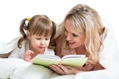 Mamá que lee un libro para embromar la mentira en la cama fotografía de archivo libre de regalías