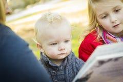 Mamá que lee un libro a sus dos niños rubios adorables imagenes de archivo