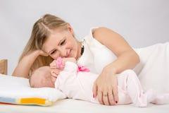 Mamá que mira cariñosamente a su bebé el mentir en la cama con él Fotos de archivo