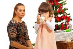 Mamá que mira a la hija que bebe la leche Imagen de archivo