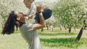 Mamá que muestra amor y el afecto al hijo Madre joven e hijo que juegan al aire libre almacen de metraje de vídeo