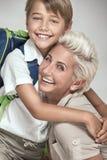 Mamá que presenta con el hijo joven, sonriendo Imagen de archivo