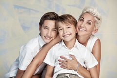 Mamá que presenta con los hijos jovenes, sonriendo Imágenes de archivo libres de regalías