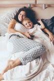 Mamá que se relaja con su pequeño hijo Imagenes de archivo